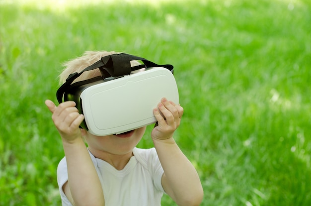 Little boy in a virtual reality helmet on surface of green grass
