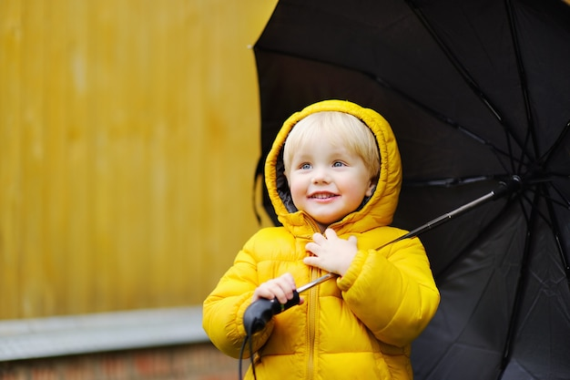 Little boy walking at rainy cloudy autumn weather. child with big black umbrella in the rain. fall outdoor activity