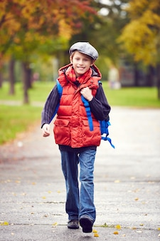 Little boy walking to school with backpack