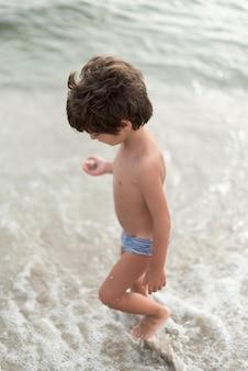 Little boy walking on seashore