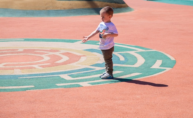 Little boy walks through the territory of the playground outdoors on sunny day