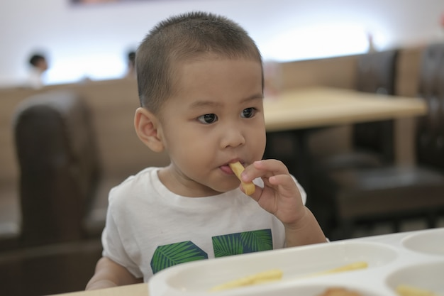 The little boy was eating lunch happily. happy a family time.