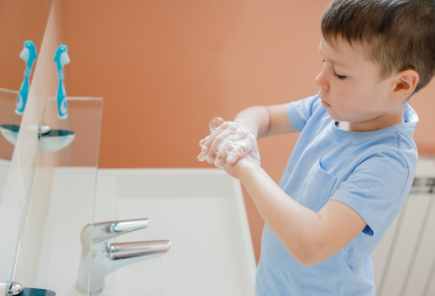 A little boy washes his hands with soap in the bathroom.