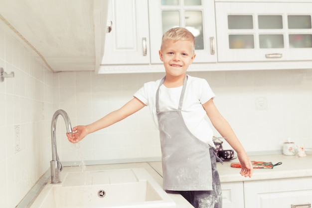 家庭の台所で手を洗う少年