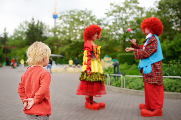 Little boy watches performance funny clowns in legoland deutschland at sunny day.