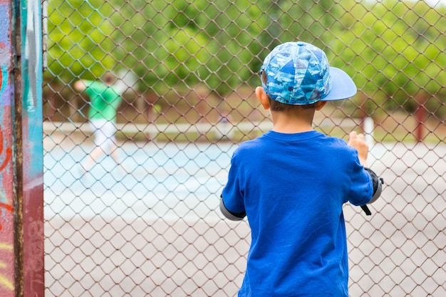 プレーヤーの金網フェンスを覗き込んでカメラに背を向けて立っているテニスの試合を見ている少年