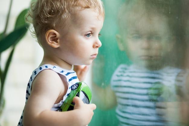 Little boy watching the rain through the window