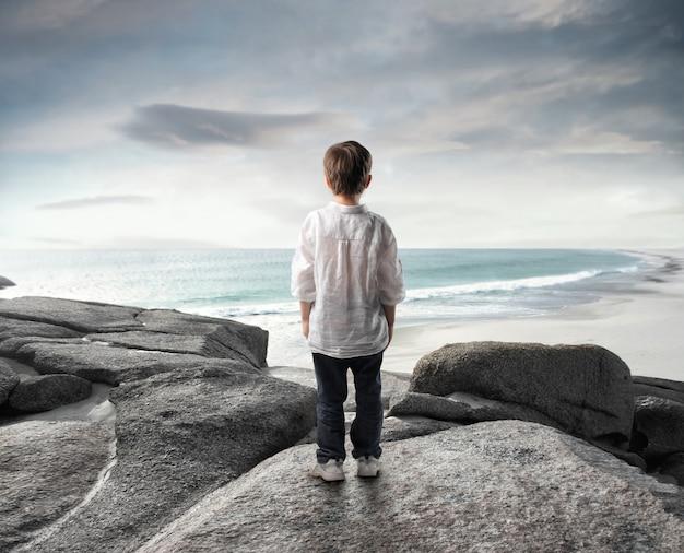 Little boy watching the sea