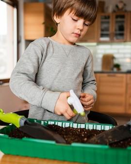 家で作物に水をまく少年