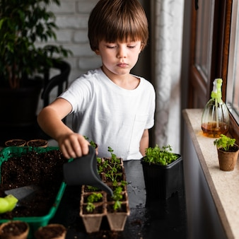 Little boy watering crops at home