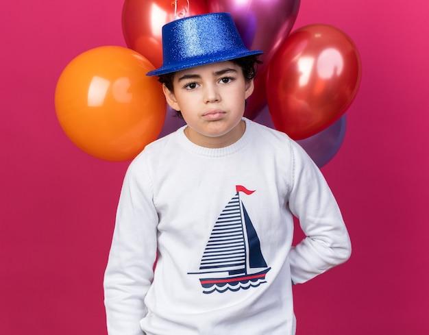 ピンクの壁に分離された前の風船に立っている青いパーティーハットを身に着けている小さな男の子