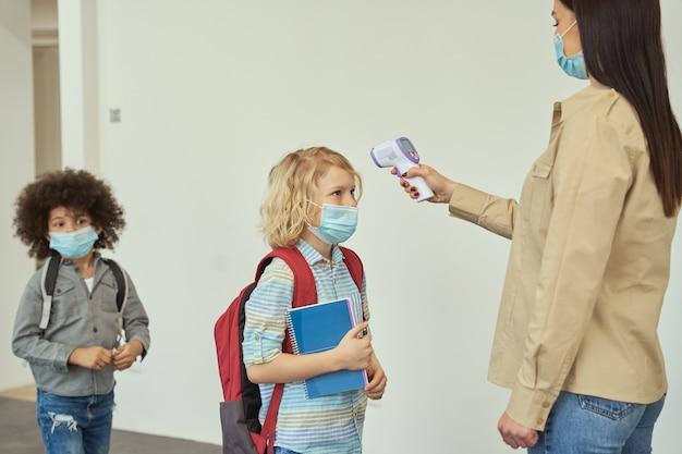 얼굴 마스크를 쓴 어린 소년이 디지털로 온도 검진 아이를 측정하는 선생님을 지켜보고 있습니다.