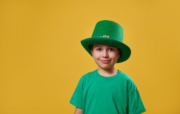 緑のtシャツとレプラコーンのアイルランドの帽子をかぶった少年がカメラを見る