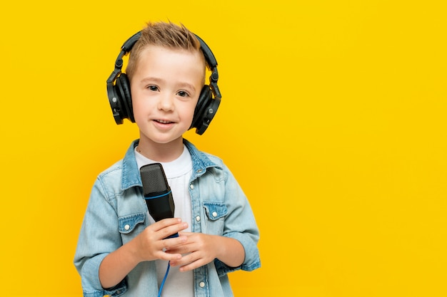 Little boy wearing headphones with a microphone in his hands