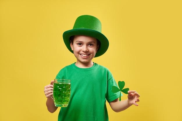 레프 러콘 요정 아일랜드 모자를 쓰고 어린 소년은 카메라에 포즈를 취하는 동안 녹색 음료와 클로버 잎 미소로 유리를 보유하고 있습니다.
