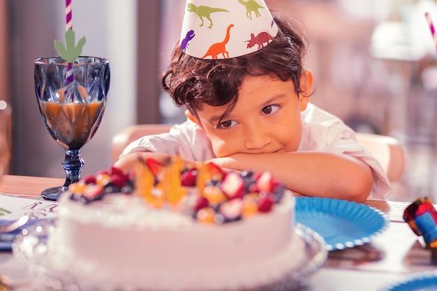 パーティーハットをかぶってバースデーケーキを見ている少年