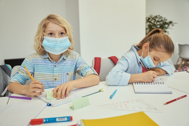 Маленький мальчик в защитной маске смотрит в сторону, внимательно слушая в начальной школе
