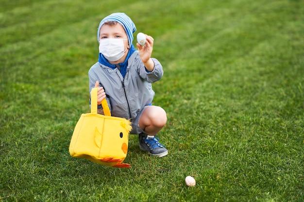 코로나 바이러스 전염병 동안 봄 정원에서 부활절 달걀에 대한 보호 마스크 사냥을 착용하는 어린 소년