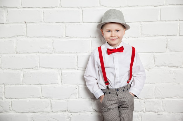 Little boy wearing a red bow tie, suspenders and white shirtand against a white brick wall