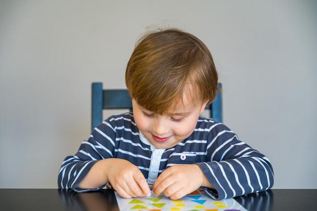 テーブルに座って、コロナウイルスの検疫中に自宅で学習している縞模様のtシャツを着た少年。形のステッカーで遊ぶ幼児。