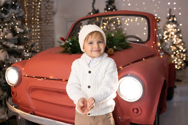 Little boy wearing winter clothes standing near red car and christmas trees in background