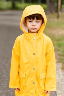 Ragazzino che indossa il cappotto di pioggia giallo
