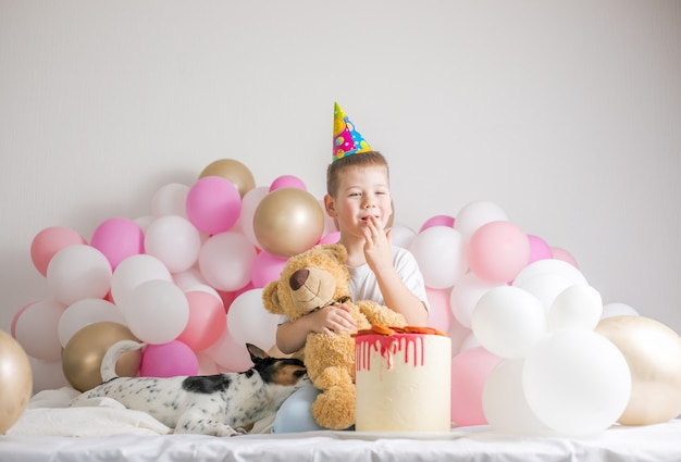 Little boy in white balloons with him dog