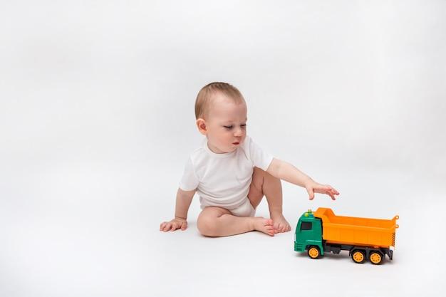Little boy in white bodysuit plays with orange car