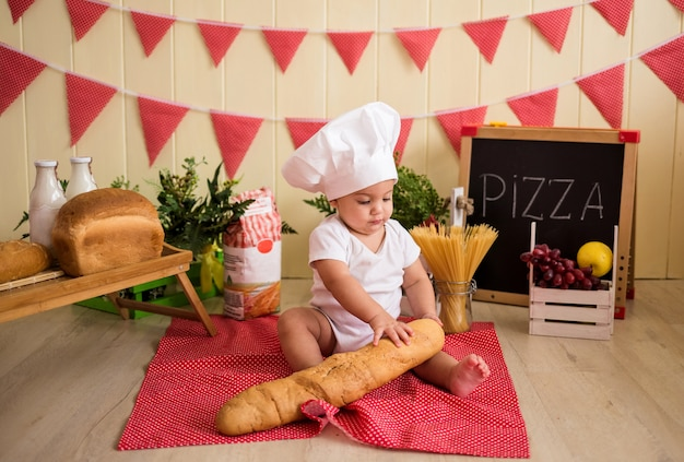 A little boy in a white chef's hat holds a loaf