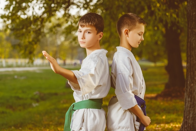 Little boy in white kimono during training karate exercises at summer outdoors