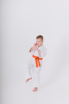 Little boy in a white kimono makes a punch on a white wall