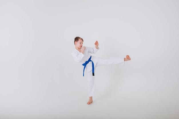 Little boy in a white kimono practices punches on a white wall