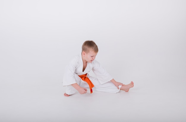Little boy in a white kimono with an orange belt does a warm-up on a white background