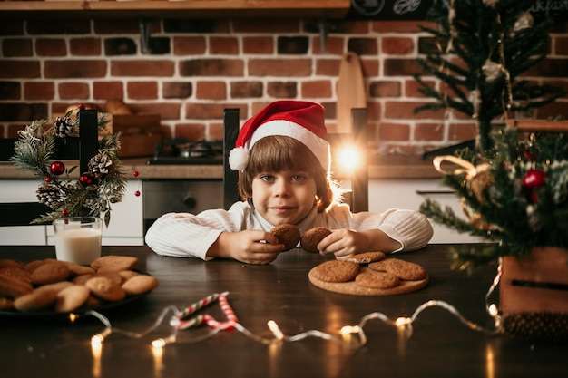 A little boy in a white knitted sweater and a new year's hat is sitting at the table and holding oatmeal cookies