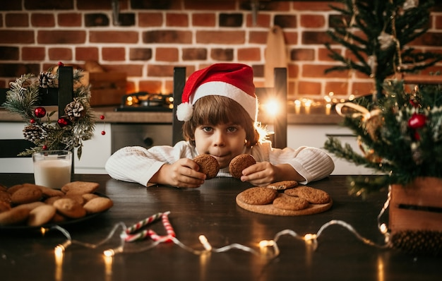 A little boy in a white knitted sweater and a red christmas hat is sitting at the kitchen table and eating oatmeal cookies