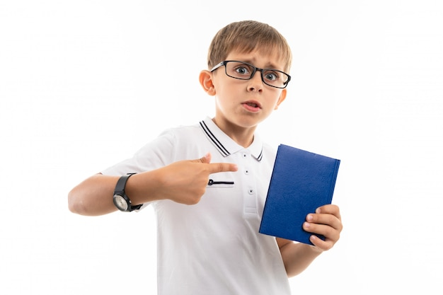 A little boy in a white shirt, blue shorts with blonde hair, black glasses with transparent glasses, a wristwatch stands and a blue notebook is on duty