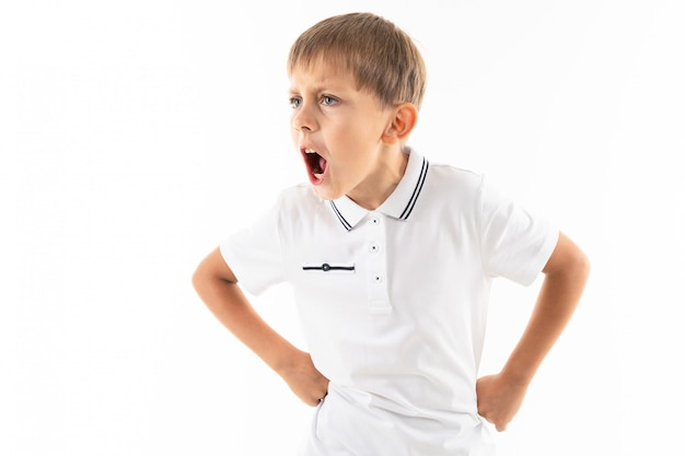 A little boy in a white shirt, blue shorts with blonde hair stands, put his hands on his belt and screams