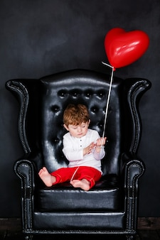 Little boy in white shirt and red trousers sitting on the armchair with red heart balloon on the  valentines day