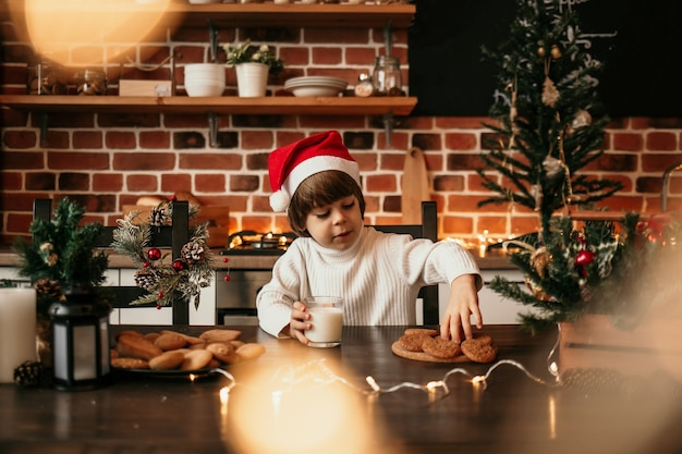 A little boy in a white sweater and a new year's hat is sitting at the kitchen table with a glass of milk and oatmeal cookies