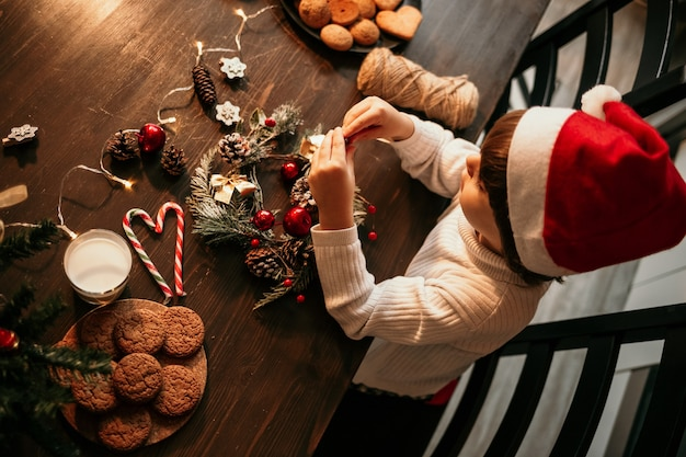 A little boy in a white sweater and a red christmas hat is sitting at the kitchen table and making a christmas wreath with his own hands