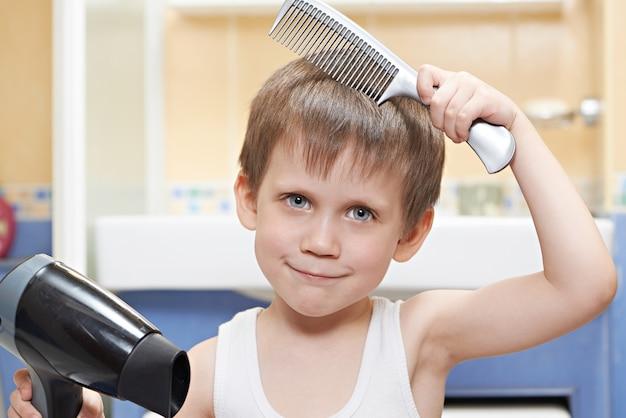 くしとヘアドライヤーを持った小さな男の子