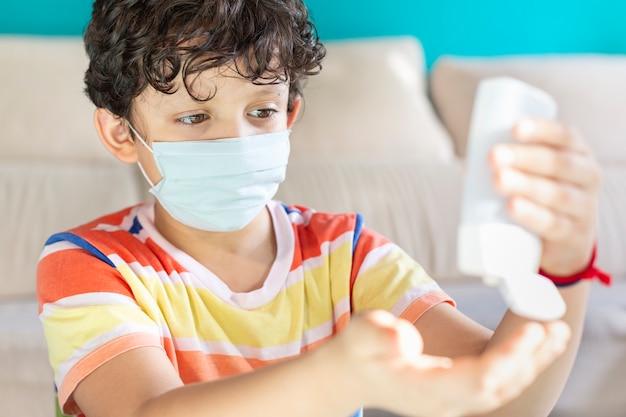 Маленький мальчик с маской для лица, применяя водно-спиртовой гель на руках