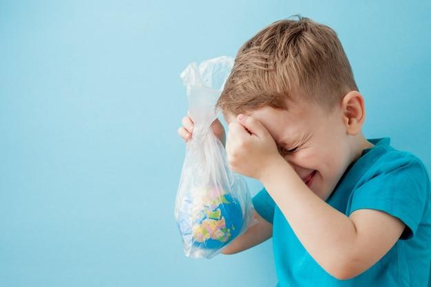 青い背景のパッケージで地球儀を持つ小さな男の子。
