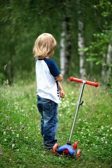 Маленький мальчик со скутером стоит на зеленой лужайке летом