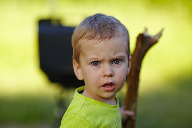 Маленький мальчик с палкой на природе