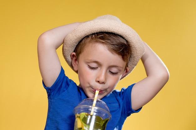 Маленький мальчик в соломенной шляпе и синей футболке пьет мохито в пластиковом стаканчике на желтом фоне