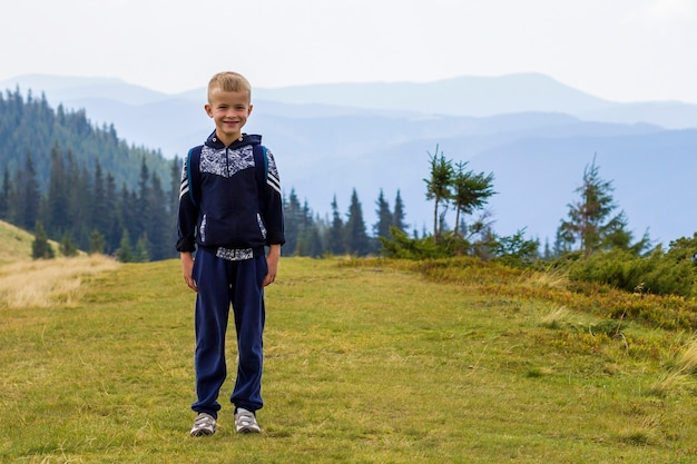 Little boy with a backpack hiking in scenic summer green carpathian mountains. child standing alone enjoying landscape mountain view. active lifestyle, adventure and weekend activity concept.