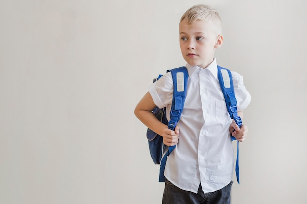 Little boy with backpack in studio