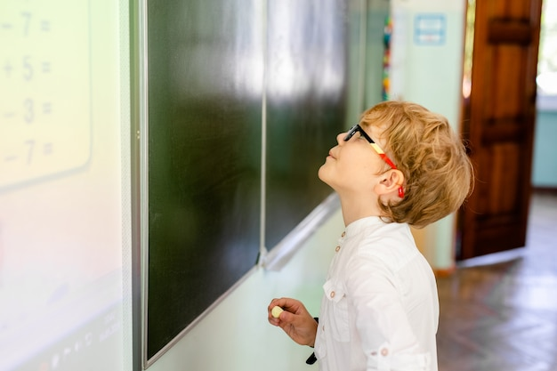 Little boy with big black glasses and white shirt standing near school blackboard with a piece of chalk making smart thinking face