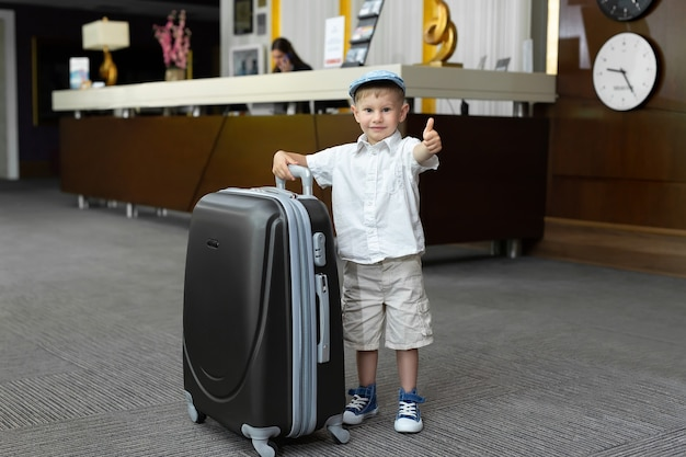 Little boy with a big suitcase in the hotel.
